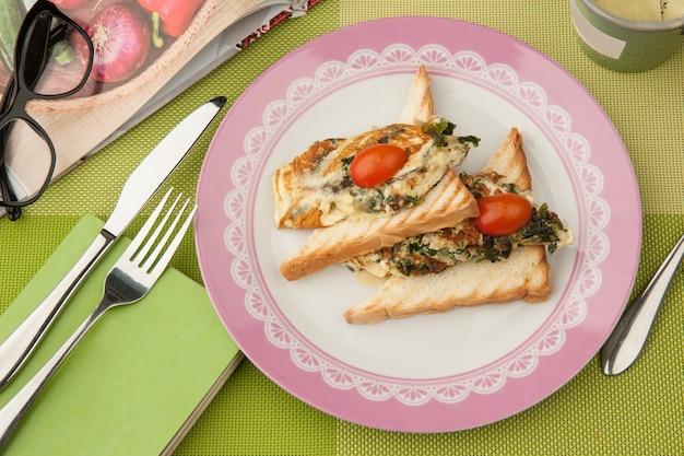 緑のテーブルクロスに本とグラスとカトラリーを添えたプレートにトマトのサンドイッチ