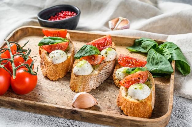 Бутерброды с помидорами, сыром моцарелла и базиликом. итальянская закуска, антипасто