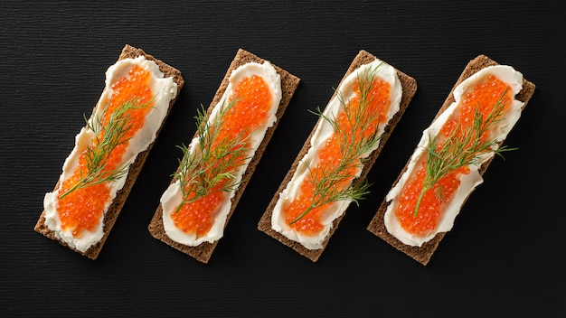 Sandwiches with trout caviar, curd cheese, dill, flat lay, keto diet.