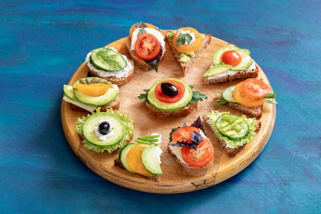 Sandwiches with vegetables, cheese and herbs on a wooden tray