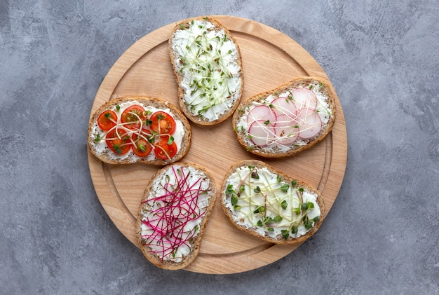 Sandwiches with vegetables and microgreens on a cutting board
