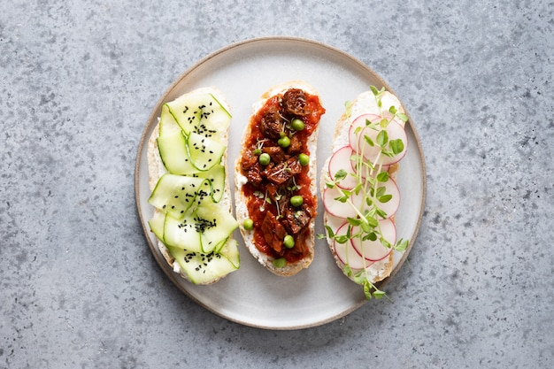Sandwiches with vegetables, radishes, tomatoes, cucumbers and microgreens on gray. top view