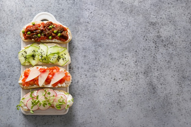Sandwiches with vegetables, radishes, tomatoes, cucumbers and microgreens on gray. view from above.