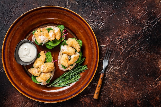 Sandwichs with fried shrimps, prawns, spinach and chard salad on a rustic plate. dark background. top view. copy space.