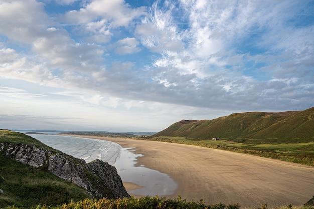 Песчаный пляж и зеленые холмы в россили