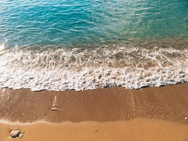 모래와 물의 모래 해변과 파도 근접 촬영 질감