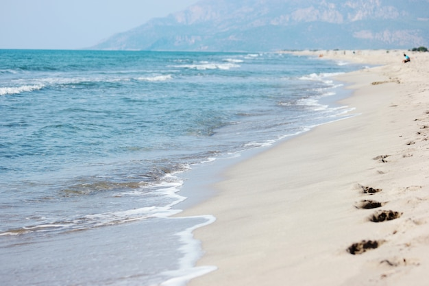 Sandy beach and blue sea waves. beautiful nature background.