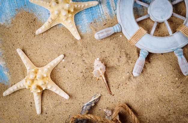 Sandy beach in old blue wood background on decorative steering wheel with starfish, seashells