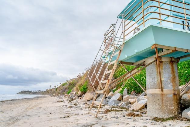 Песчаный пляж на пляже в лос-анджелесе голубые башни спасателей на закате на побережье калифорнии