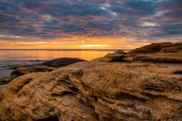 Sandy beach rocks colored in orange under the rays of the rising sun.