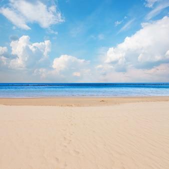 Песчаный пляж на берегу моря с голубым небом