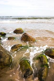 바람이 부는 날씨에서 거품과 파도, 여름 풍경과 모래 해변 바다