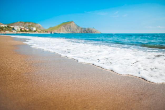 배경에 산 모래 해변입니다. 산은 풀로 덮여 있고 바다에서 깎아 지른 절벽이 있습니다. 하늘이 맑다