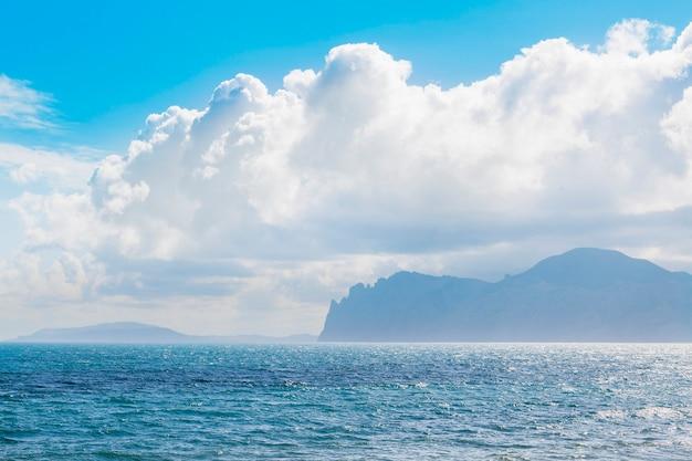 背景に山と砂浜。山々は草で覆われ、海からの断崖があります。空は曇りです