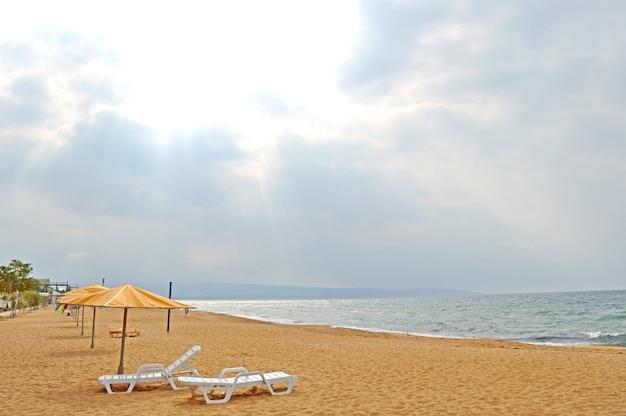 우산, 갑판 의자가있는 모래 해변. 사람없이