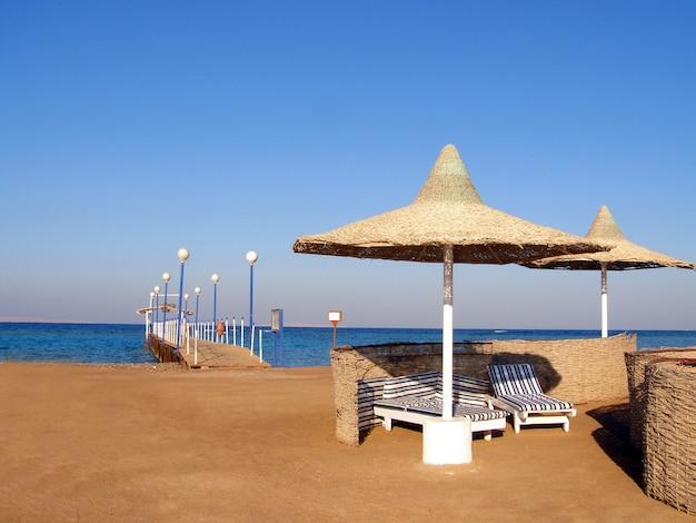 Песчаный пляж с зонтиками, шезлонгами и пирсом на побережье египта.