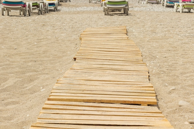 Sandy beach, wooden boards and lounge chairs in the distance