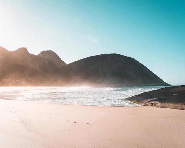 Песчаный берег красивого моря с ясным голубым небом и солнечным светом