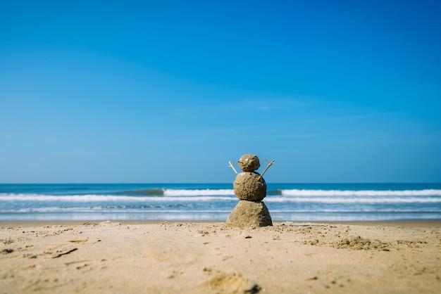 青い曇り夏空に対して海のビーチで砂浜の幸せな男-旅行の概念。