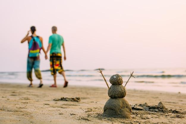 歩いているゲイの男性のカップルに対して海のビーチで砂浜の幸せな男