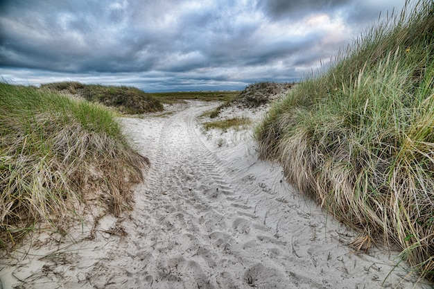 Sandy pathway surrounded by hill under the cloudy sky