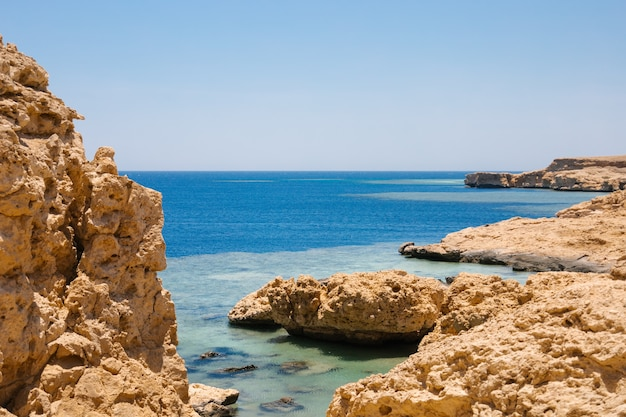 Sandy and rocky coast with blue color of water desolate beach on the coast shore of red sea ras muha...