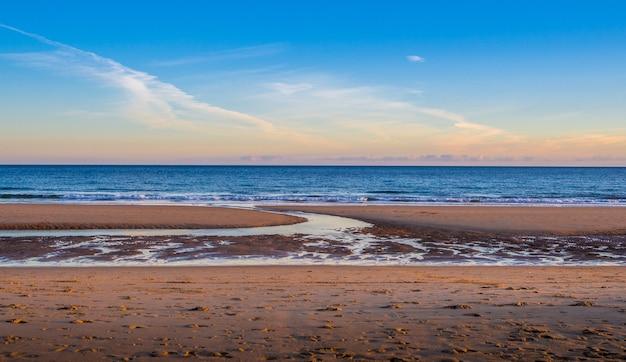 Песчаный берег моря с чистым небом