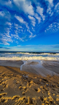 Sandy shore with foaming waves and a blue sky with clouds