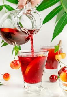 Напиток сангрии, льющийся из кувшина в стакан на белом фоне. освежающий летний напиток.