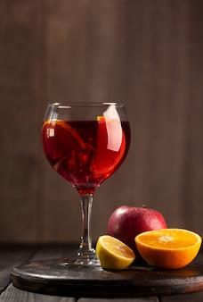 Sangria in glass with ingredients - orange, lemon and apple, dark wooden background