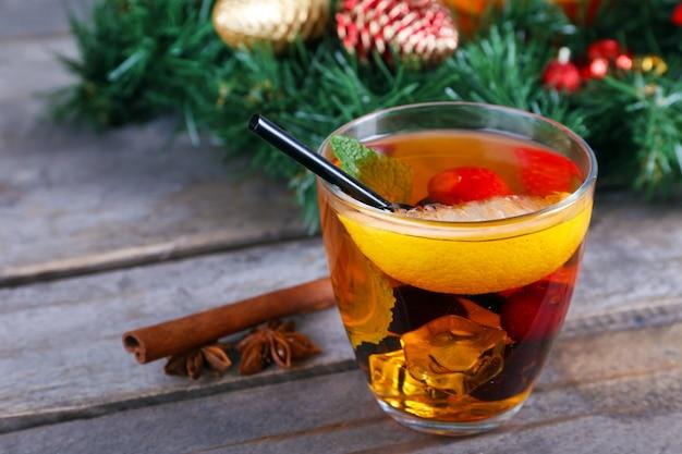 Сангрия в миске и стакане с рождественскими украшениями на деревянном столе крупным планом