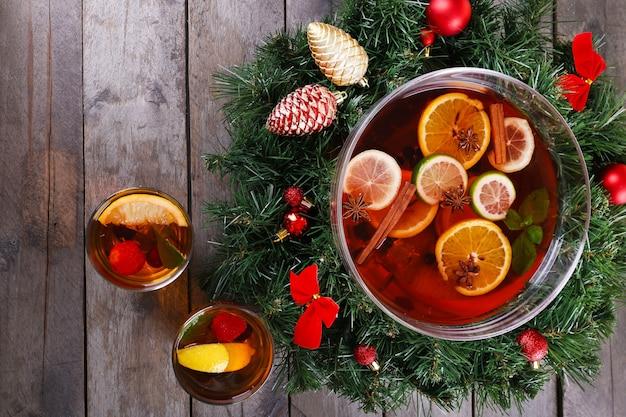木製のテーブルにクリスマスの装飾が施されたボウルとグラスのサングリアをクローズアップ