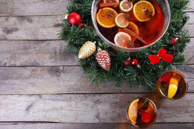 Сангрия в миске и очках с рождественским украшением на деревянном столе крупным планом