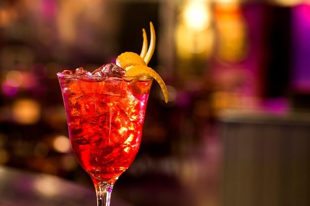 ガラスのサングリア-オレンジ、レモン、ライムのスライス、砂糖、暗いバーの背景。