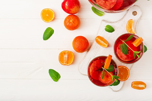 Sangria with fruits and mint on a white