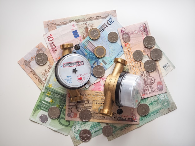 Sanitary engineering. water meters and banknotes euro and arab dirhams. the concept of saving water.