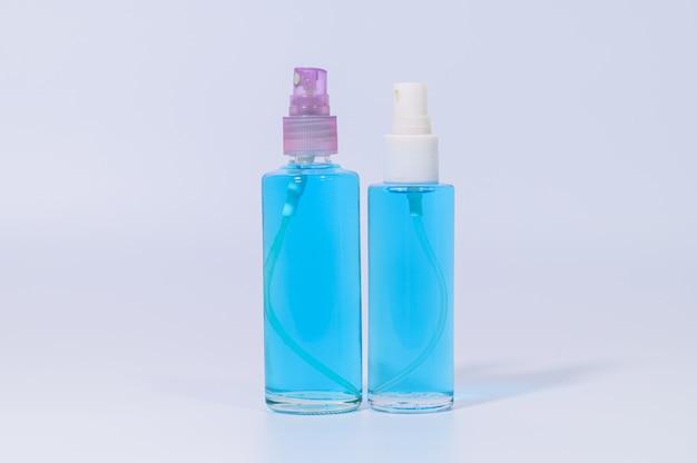手を洗うためのアルコールジェル入りのサニタリーマスクコロナウイルスやcovic-19病原体を防ぎます。白い壁のシーン