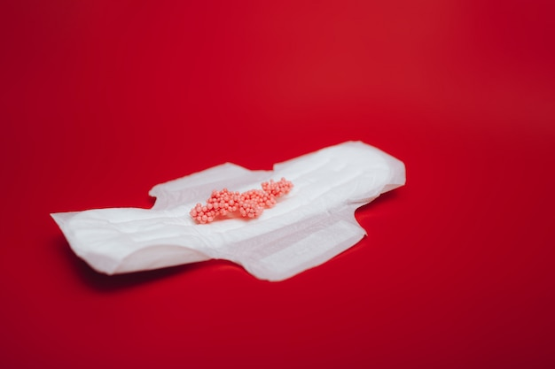 Sanitary napkin with red balls imitating menstruation on a red surface
