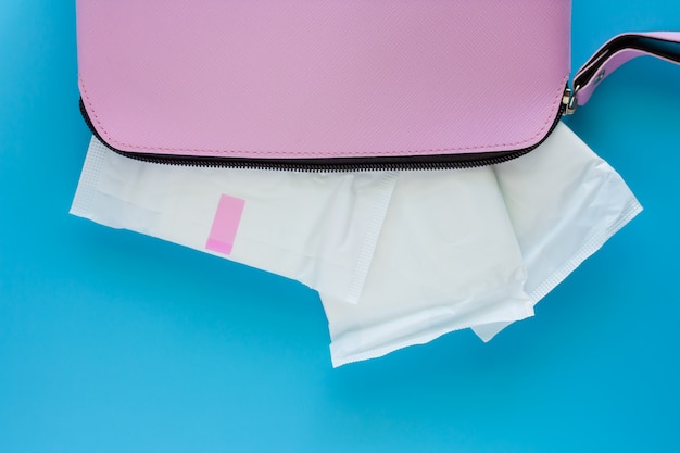 Sanitary napkin in women's pink bag on blue background