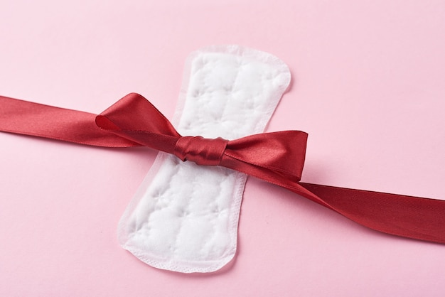Sanitary pad and red ribbon on a pink background