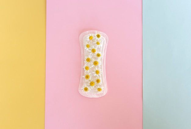 A sanitary pad with chamomile flowers on it lies on a colorful background. menstruation days. hygiene and freshness concept