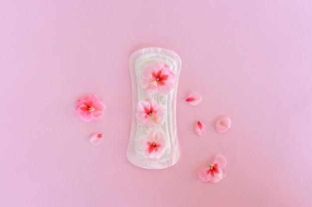 A sanitary pad with flowers on it lies on a yellow background. menstruation days. hygiene and freshness concept