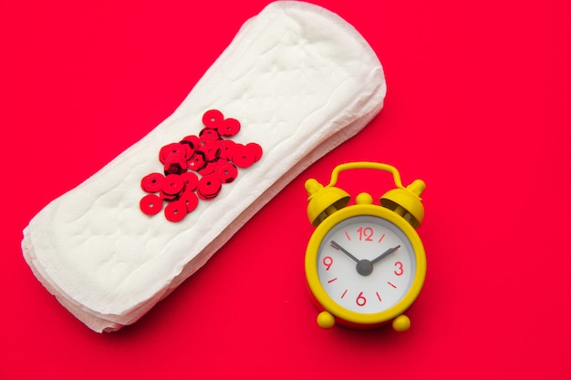 Sanitary pads and alarm clock on red