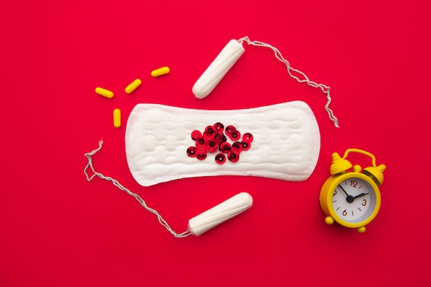 Sanitary pads and tampons, alarm clock and hormonal contraceptive on red.