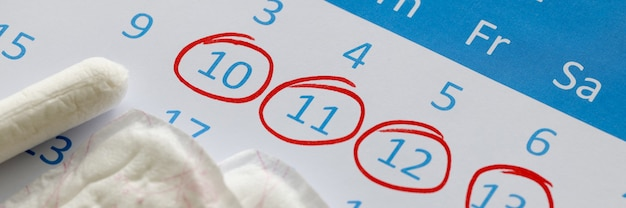 Sanitary pads and tampons are on calendar. numbers are circled in red pen. female menstrual cycle concept