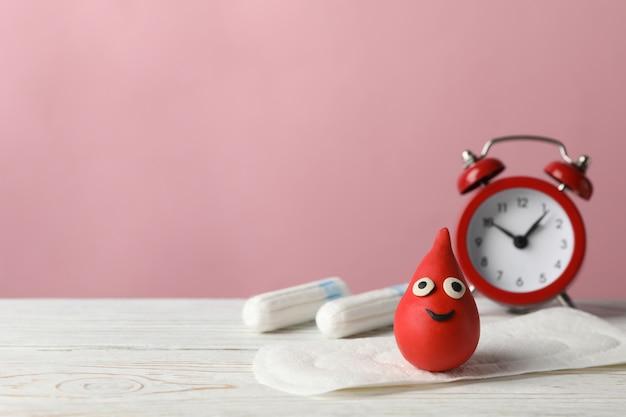 羽、装飾的な血の低下、木製のテーブル、コピー領域の目覚まし時計付き生理用ナプキン
