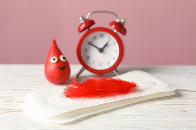 羽、装飾的な血の滴、木製のテーブルに目覚まし時計付き生理用ナプキン