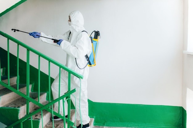 Sanitary professional worker wearing hazmat suit disinfects a staircase entryway block of flats. coronavirus prevention measures at residential areas.