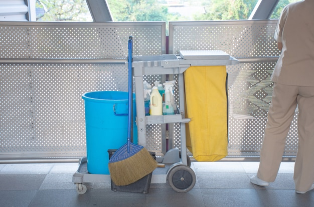Sanitary set on tray with cleaning man,bottle of hygiene liquid with mop and bloom and bin for clean public area.
