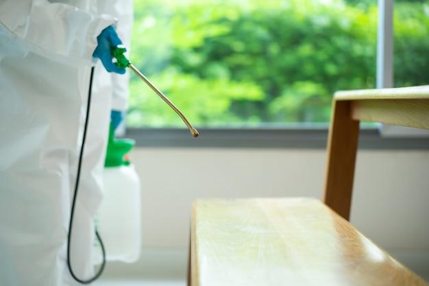 建物内の表面を消毒する衛生スタッフは、コロナウイルスまたはcovid-19病のパンデミックを引き起こします。 covid19ウイルスから消毒するために表面に洗浄剤スプレーを使用する洗浄作業員。
